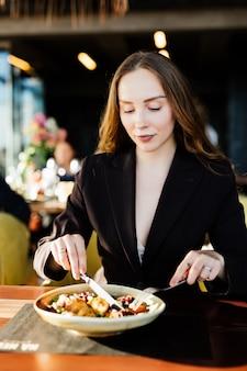 Junge schönheitsfrau, die gesundes essen isst, das im schönen innenraum mit grünen blumen sitzt