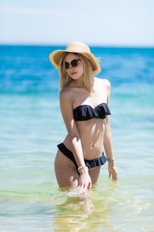 Junge schönheitsfrau im schwarzen bikini und im strohhut, die im ozeanwasser am strand gehen.