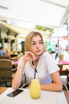 Junge schönheitsfrau mit cocktail im straßencafé