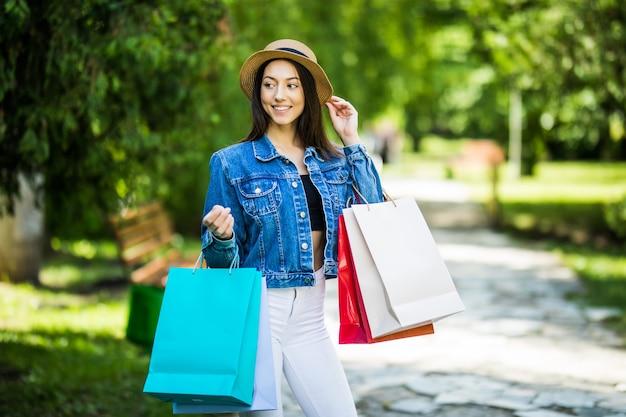 Junge schönheitsfrau mit einkaufstaschen, die im stadtpark gehen