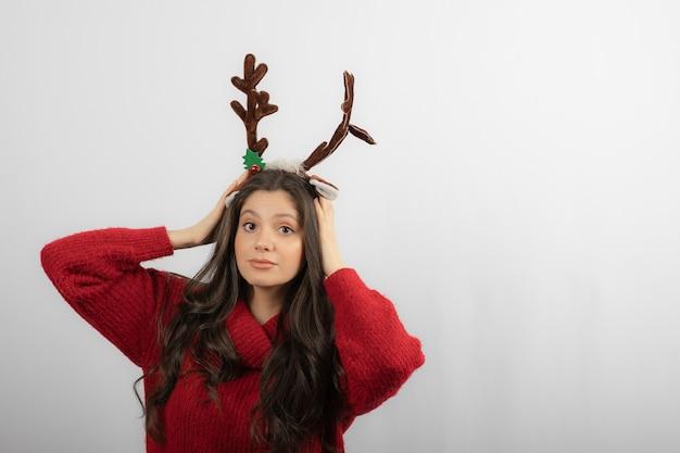 Junge schönheitsfrau mit weihnachtsstirnband wie hirschhörner im roten winterpullover.