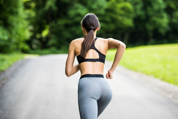 Junge schönheitsfußball-fitnessfrau, die im städtischen park im freien läuft