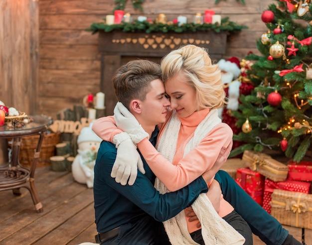Junge schönheitsmodebraut im winter glückliche paarliebhaber gratulieren einander mit weihnachten. dekorierter weihnachtsbaum, feiertags- und neujahrskonzept.