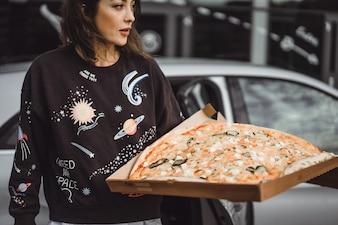 Junge schöne Frau, die eine Scheibe der Pizza auf Stadtstraße isst