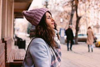 Junge schöne Frau im Mantel und im Hut im Spätherbst oder im frühen Winter auf Stadtstraße enjoyi