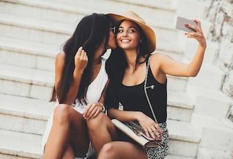 Junge schöne lächelnde Frau im Hut, der draußen selfie mit Smartphone macht