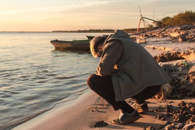 Junge schreiben in den sand am ufer des meeres.