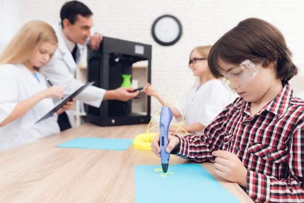 Junge schreibt durch stift 3d während einer lektion in der klasse.