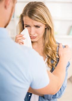 Junge schreiende frau während ehemann, der sie beruhigt.