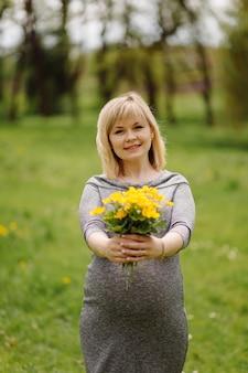 Junge schwangere blonde frau im grauen kleid, schwangeres mädchen im frühjahr auf einem spaziergang, mutterschaftskonzept