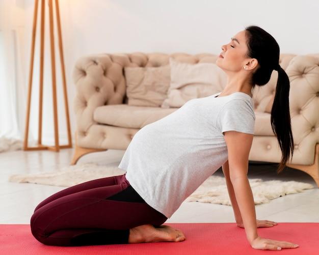 Junge schwangere frau der seitenansicht, die auf eignungsmatte ausübt
