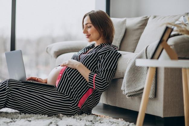 Junge schwangere frau, die am computer zu hause arbeitet