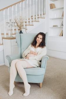 Junge schwangere frau, die auf einem sessel sitzt