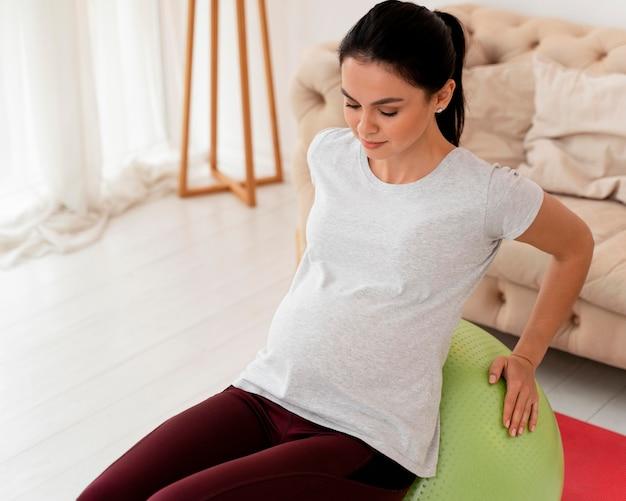 Junge schwangere frau, die auf fitnessball ausübt