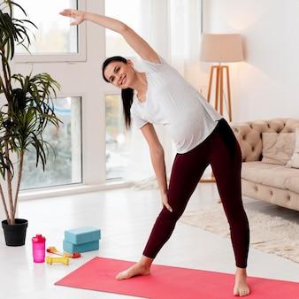 Junge schwangere frau, die auf fitnessmatte ausübt