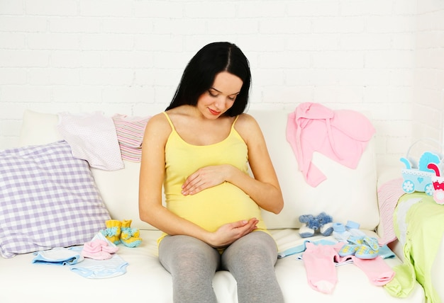Junge schwangere frau, die auf sofa, nahaufnahme entspannt
