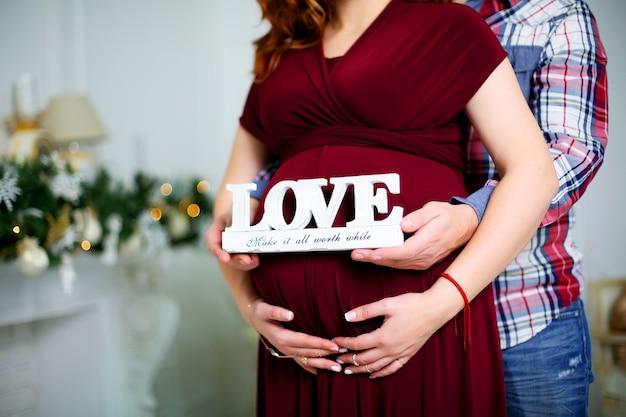 Junge schwangere frau, die blöcke mit buchstaben macht, die wortliebe bilden
