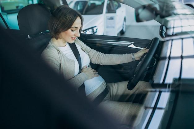 Junge schwangere frau, die ein auto im autoausstellungsraum testend