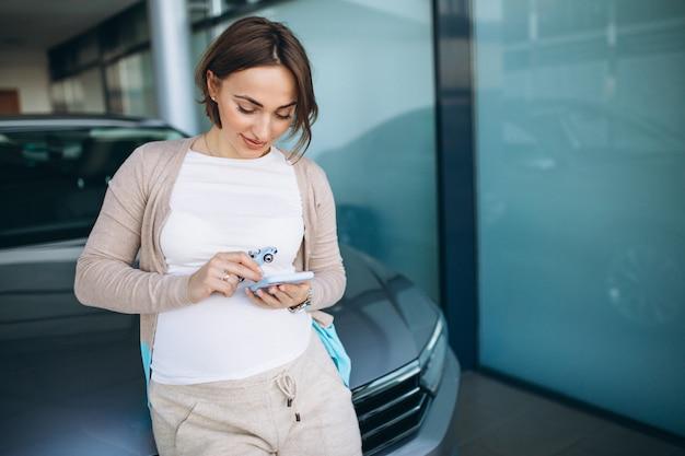 Junge schwangere frau, die ein auto in einem autoausstellungsraum wählt