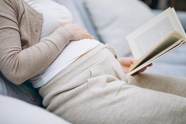 Junge schwangere frau, die ein buch zu hause liest
