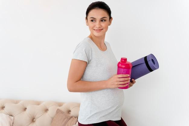 Junge schwangere frau, die eine fitnessmatte hält
