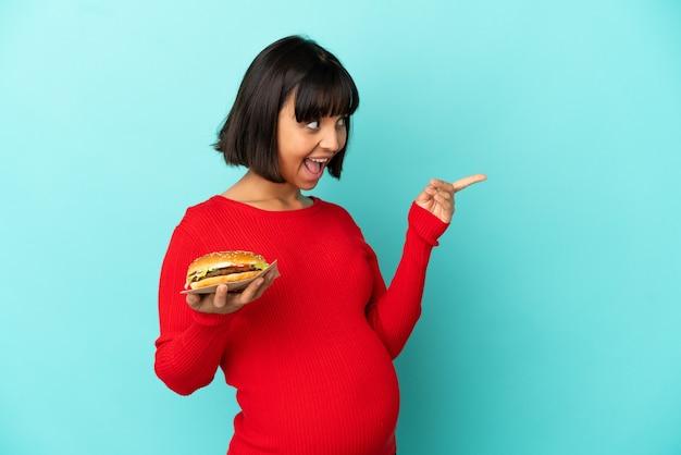 Junge schwangere frau, die einen burger über isoliertem hintergrund hält und beabsichtigt, die lösung zu realisieren, während sie einen finger hochhebt