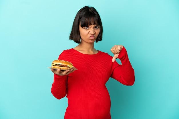 Junge schwangere frau, die einen burger über isoliertem hintergrund hält und daumen nach unten mit negativem ausdruck zeigt