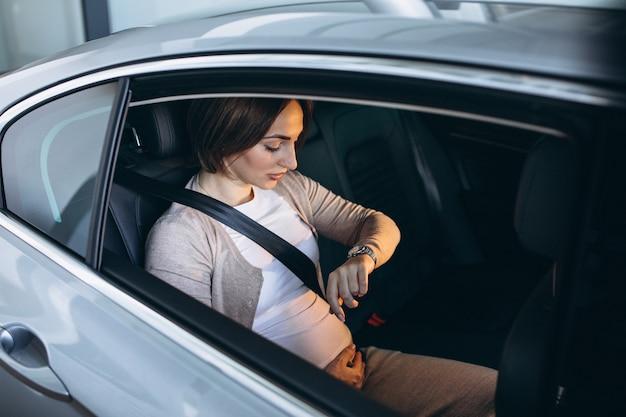 Junge schwangere frau, die im auto zum krankenhaus fährt