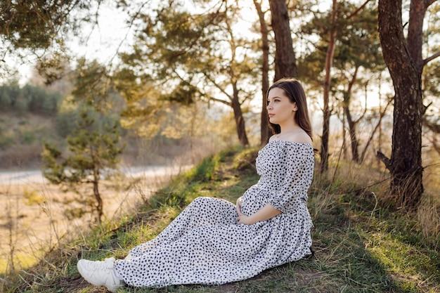 Junge schwangere frau, die im park draußen entspannt