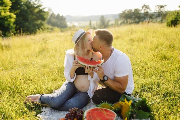 Junge schwangere frau, die im park draußen mit ihrem mann entspannt