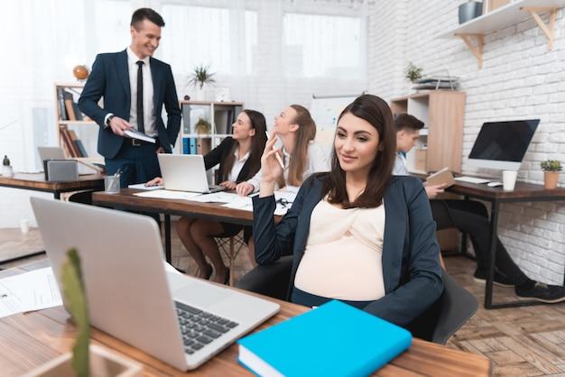 Junge schwangere frau, die innerhalb des büros arbeitet