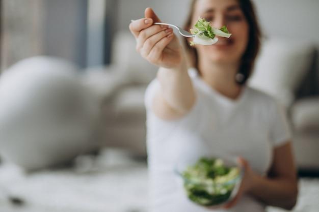 Junge schwangere frau, die salat zu hause isst
