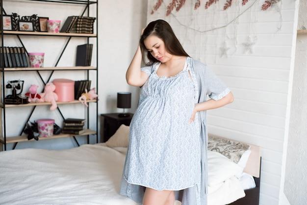 Junge schwangere frau, die sich zu hause schlecht fühlt