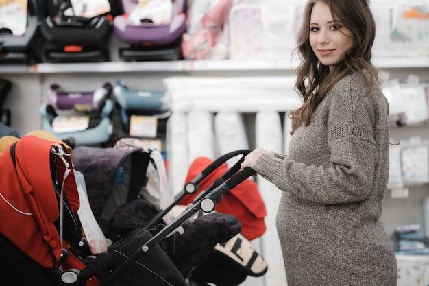 Junge schwangere frau, die sorgfältig kinderwagen oder kinderwagen für neugeborene wählt.