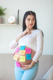 Junge schwangere frau, die versucht, sachen ins krankenhaus nicht zu vergessen. erwartende frau mit notizen auf dem bauch.