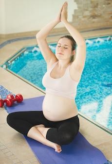 Junge schwangere frau, die yoga auf der seite des swimmingpools tut