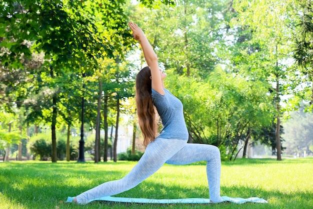 Junge schwangere frau, die yoga im freien praktiziert