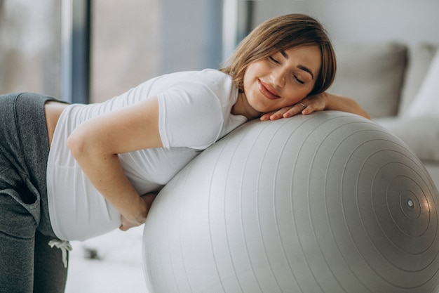 Junge schwangere frau, die yoga mit passendem ball zu hause ausübt
