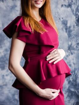 Junge schwangere frau im roten kleid legte ihre hände auf ihren bauch