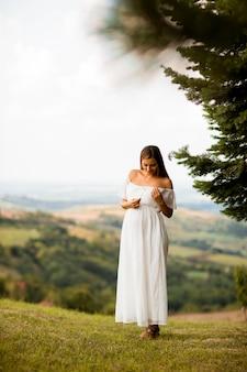 Junge schwangere frau im weißen kleid am wald an einem sommertag