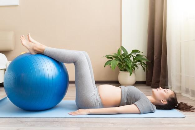Junge schwangere frau im zweiten trimester macht fitnessübungen