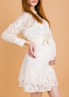Junge schwangere frau in einem weißen kleid legte ihre hände auf ihren bauch