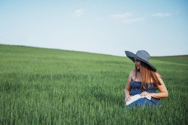 Junge schwangere frau in einem weizenfeld