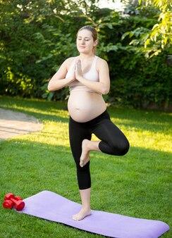 Junge schwangere frau macht yoga-übung auf gras
