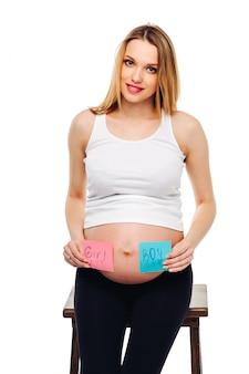 Junge schwangere frau mit einem aufkleber und einer frage auf jungen- oder mädchenkonzept. werdende mutter.