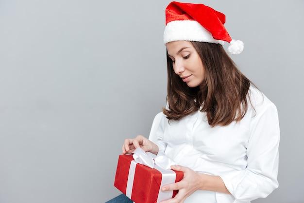 Junge schwangere frau mit geschenk in weihnachtsmütze im studio isoliert grauen hintergrund