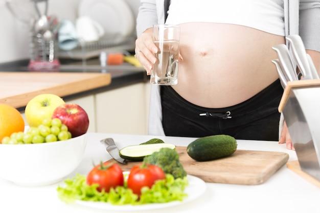 Junge schwangere frau mit glas wasser auf küche