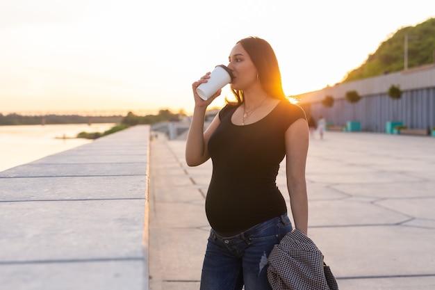 Junge schwangere frau trinkt kaffee oder tee zum mitnehmen auf dem damm mutterschaft freizeit und gesundheit