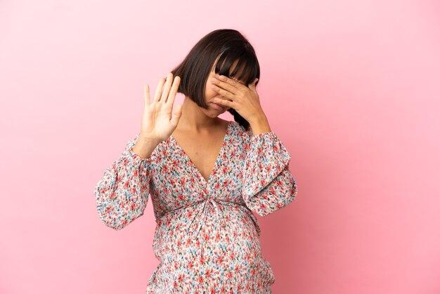 Junge schwangere frau über isolierte rosa oberfläche, die stoppgeste macht und gesicht bedeckt