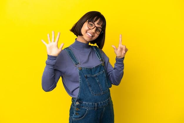 Junge schwangere frau über isoliertem gelbem hintergrund, der mit den fingern sieben zählt
